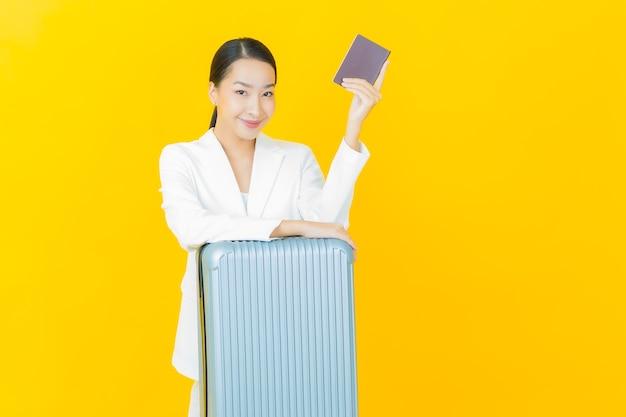 Schöne junge asiatische frau des porträts mit gepäcktasche und reisepass bereit für die reise