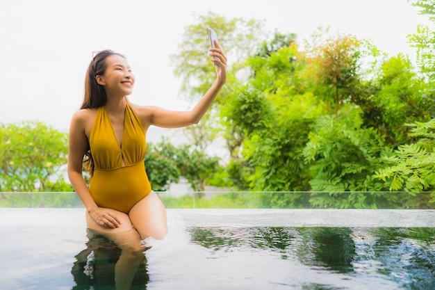 Schöne junge asiatische frau des porträts mit handy oder handy um swimmingpool am hotelerholungsort