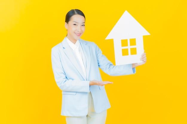 Schöne junge asiatische frau des porträts mit haus- oder hauptpapierzeichen auf gelb