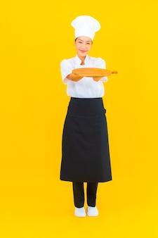 Schöne junge asiatische frau des porträts mit hölzernem schneidebrett auf gelbem lokalisiertem hintergrund