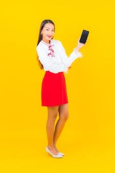Schöne junge asiatische frau des porträts mit intelligentem handy auf gelb