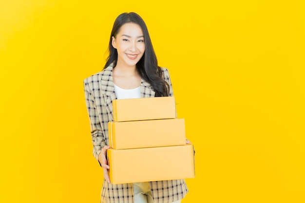 Schöne junge asiatische frau des porträts mit kasten bereit für den versand