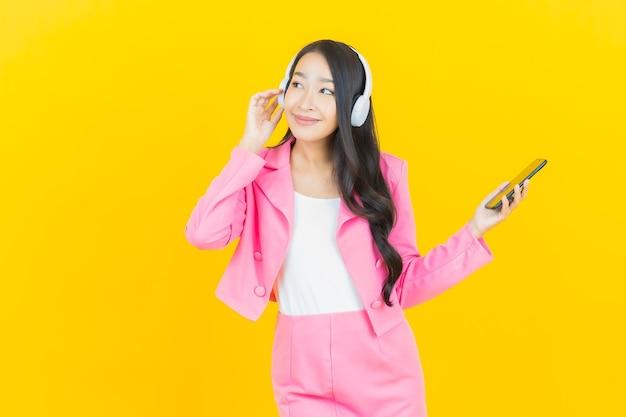 Schöne junge asiatische frau des porträts mit kopfhörer und smartphone zum musikhören auf gelber wand