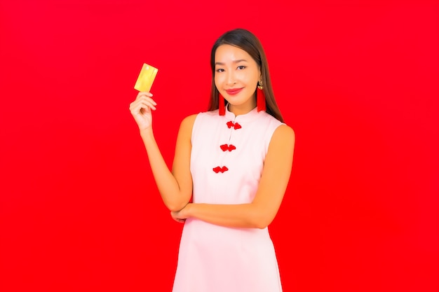 Schöne junge asiatische frau des porträts mit kreditkarte auf roter isolierter wand