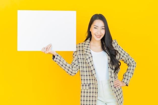 Schöne junge asiatische frau des porträts mit leerem weißem plakat