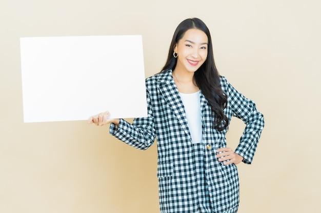 Schöne junge asiatische frau des porträts mit leerer weißer anschlagtafel auf beige