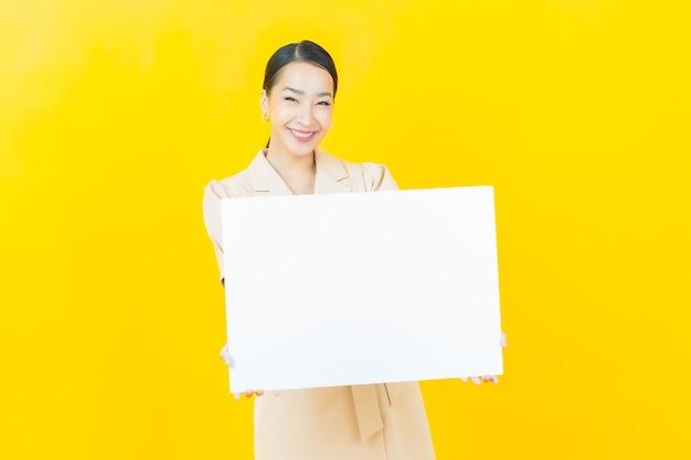 Schöne junge asiatische frau des porträts mit leerer weißer anschlagtafel auf farbwand