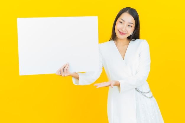 Schöne junge asiatische frau des porträts mit leerer weißer anschlagtafel