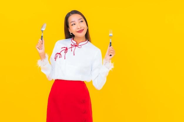 Schöne junge asiatische frau des porträts mit löffel und gabel auf gelb