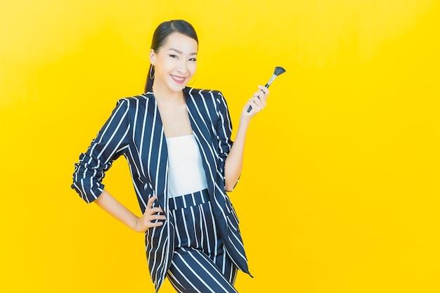 Schöne junge asiatische frau des porträts mit make-upbürstenkosmetik auf farbhintergrund