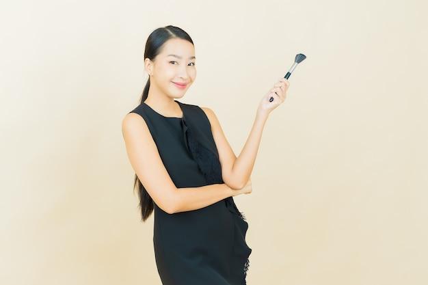 Schöne junge asiatische frau des porträts mit make-upbürstenkosmetik auf farbwand