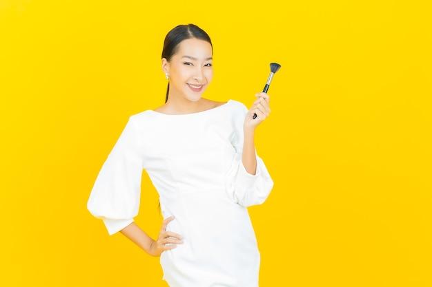 Schöne junge asiatische frau des porträts mit make-upbürstenkosmetik auf gelb