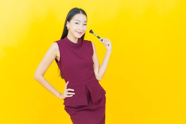 Schöne junge asiatische frau des porträts mit make-upbürstenkosmetik auf gelber wand