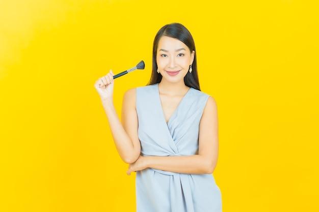 Schöne junge asiatische frau des porträts mit make-upbürstenkosmetik
