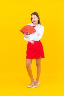 Schöne junge asiatische frau des porträts mit rotem briefumschlag auf gelb
