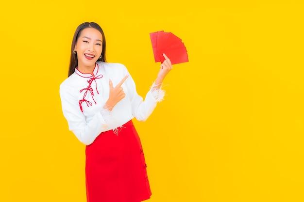 Schöne junge asiatische frau des porträts mit rotem briefumschlag im chinesischen neuen jahr auf gelb Kostenlose Fotos