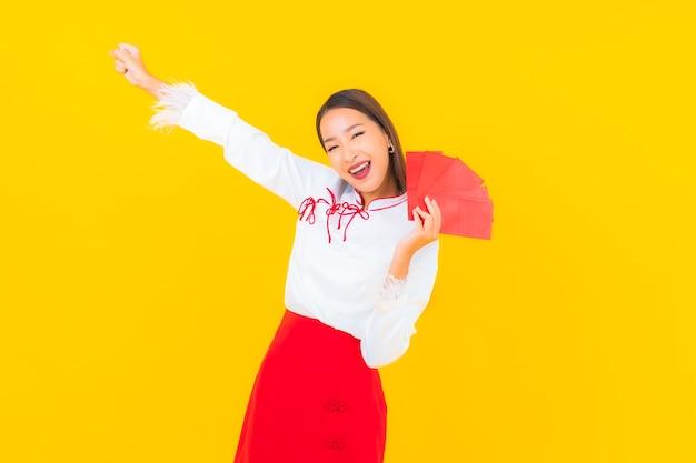 Schöne junge asiatische frau des porträts mit rotem briefumschlag im chinesischen neuen jahr auf gelb