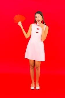 Schöne junge asiatische frau des porträts mit rotem umschlagbrief auf roter wand