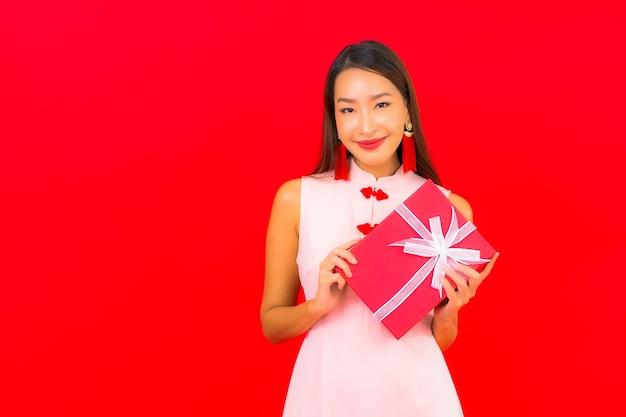 Schöne junge asiatische frau des porträts mit roter geschenkbox auf roter isolierter wand