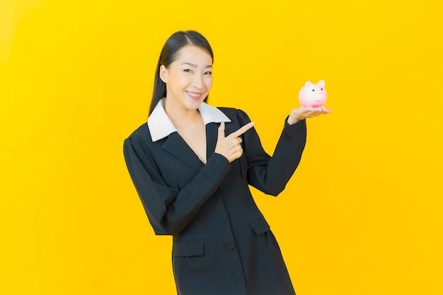 Schöne junge asiatische frau des porträts mit sparschwein auf farbwand