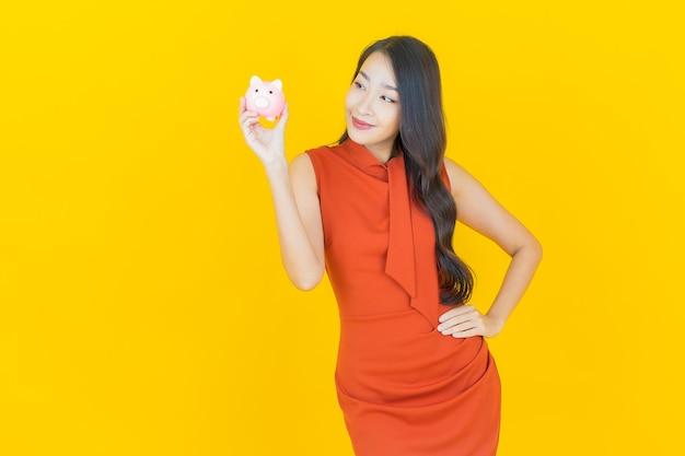 Schöne junge asiatische frau des porträts mit sparschwein auf gelb