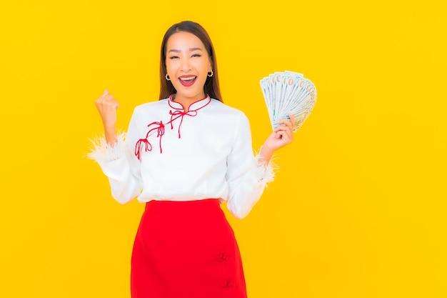 Schöne junge asiatische frau des porträts mit viel bargeld und geld auf gelb