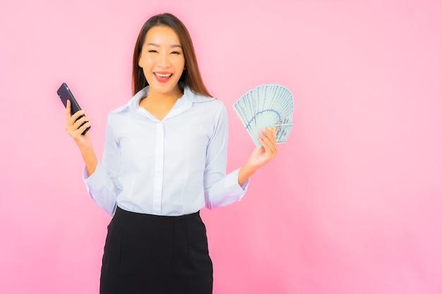 Schöne junge asiatische frau des porträts mit viel bargeld und geld auf rosa wand