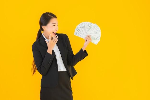 Schöne junge asiatische frau des porträts mit viel geld