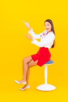 Schöne junge asiatische frau des porträts sitzen auf stuhl auf gelb