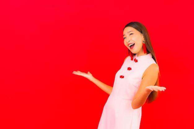 Schöne junge asiatische frau des porträts tragen chinesische kleidung des neuen jahres auf roter wand