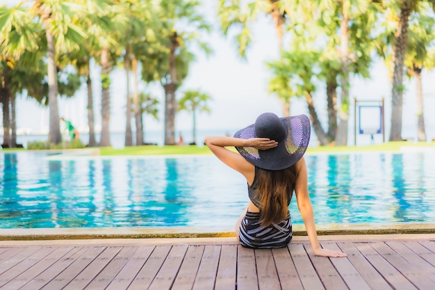 Schöne junge asiatische frau des porträts um swimmingpool