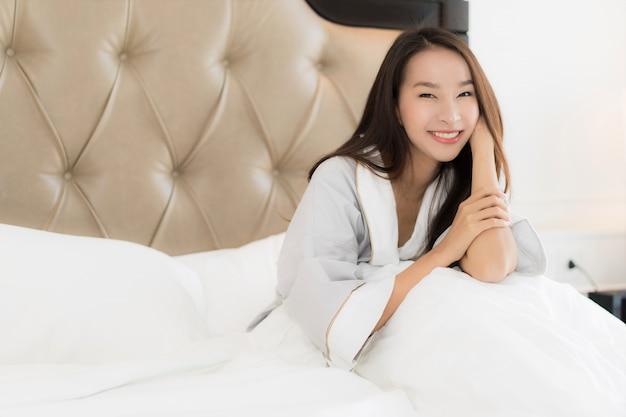 Schöne junge asiatische frau des portraits wachen mit glücklichem auf und lächeln auf bett im schlafzimmerinnenraum