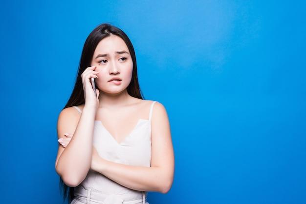 Schöne junge asiatische frau, die am telefon an der blauen wand spricht