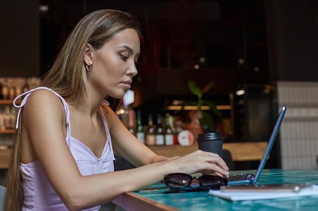 Schöne junge asiatische frau, die am tisch des cafés sitzt und am laptop arbeitet