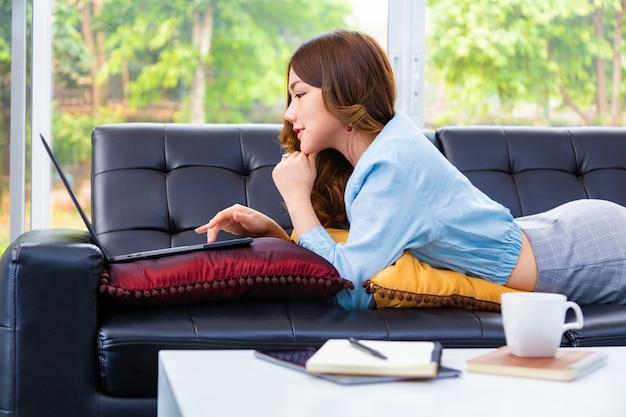 Schöne junge asiatische frau, die an ihrem computer in ihrem wohnzimmer zu hause arbeitet