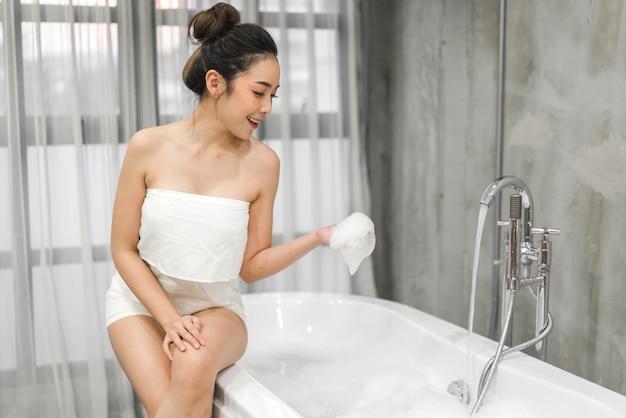 Schöne junge asiatische frau, die auf badewanne sitzt