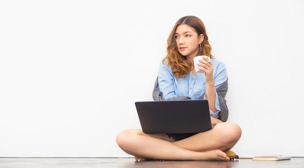 Schöne junge asiatische frau, die auf dem boden sitzt und eine tasse kaffee hält, während sie eine pause von der arbeit an ihrem computer zu hause macht Premium Fotos