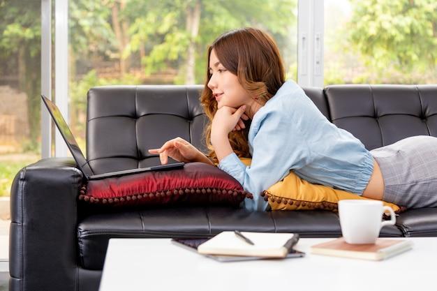 Schöne junge asiatische frau, die auf ihrer couch liegt, während sie an ihrem computer in ihrem wohnzimmer zu hause arbeitet