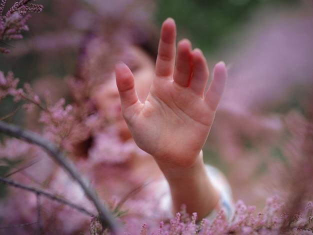 Schöne junge asiatische frau, die das blühen der blumen im frühjahr genießt. nacktes make-up. nahaufnahme porträt in rosa büschen