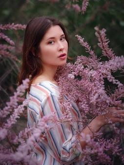 Schöne junge asiatische frau, die das blühen der blumen im frühjahr genießt. nacktes make-up. nahaufnahme porträt