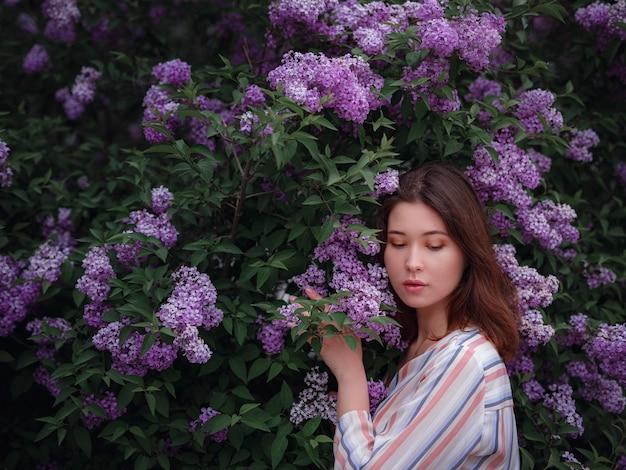 Schöne junge asiatische frau, die das blühen der blumenflieder im frühjahr genießt. nacktes make-up. nahaufnahme porträt in schönen lila fliederbüschen