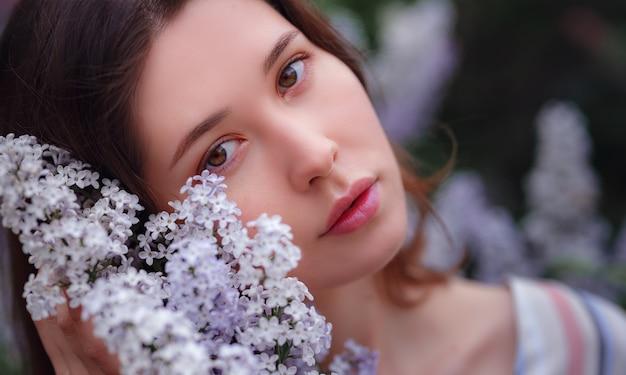 Schöne junge asiatische frau, die das blühen der blumenflieder im frühjahr genießt. nacktes make-up. nahaufnahme porträt