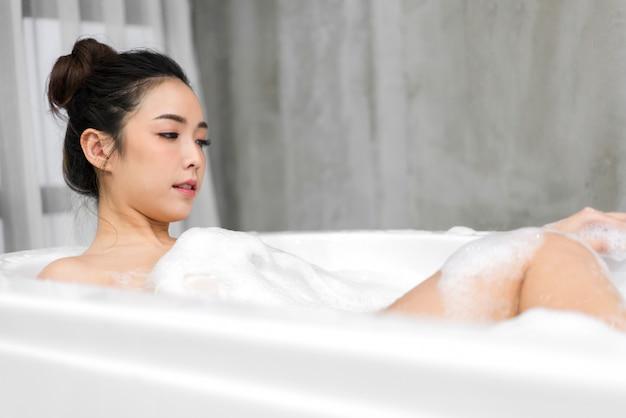 Schöne junge asiatische frau, die ein bad mit blasenschaum nimmt