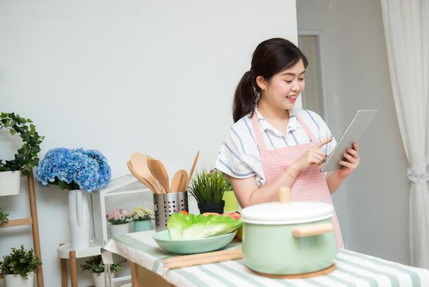 Schöne junge asiatische frau, die eine digitale tablette in der küche verwendet