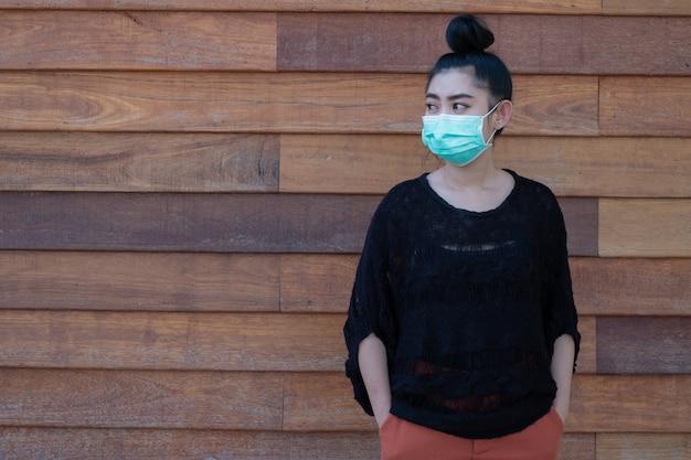 Schöne junge asiatische frau, die eine medizinische maske trägt