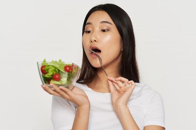 Schöne junge asiatische frau, die einen gesunden salat isst