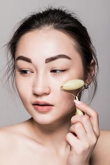 Schöne junge asiatische frau, die einen jadegesichtsroller auf ihrer makellosen haut verwendet. schönheitsgesichtsnahaufnahme. konzeptionelle gesichtsbehandlungen mit halbedelsteinen. isoliert auf grau mit kopierraum