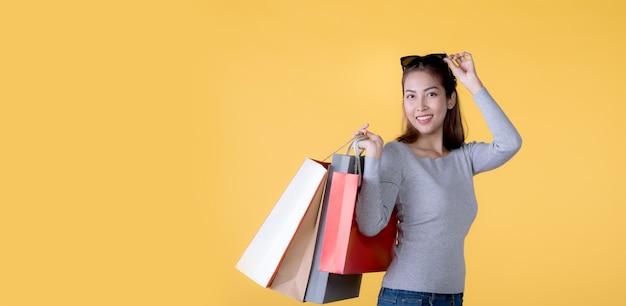Schöne junge asiatische frau, die einkaufstaschen trägt, die glücklich lokalisiert auf gelbem fahnenhintergrund mit kopienraum suchen