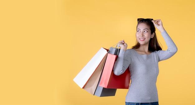Schöne junge asiatische frau, die einkaufstaschen trägt, die überrascht und glücklich lokalisiert auf gelbem fahnenhintergrund mit kopienraum suchen