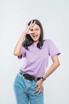 Schöne junge asiatische frau, die glückliche show ok-zeichen über ihrem auge lächelt